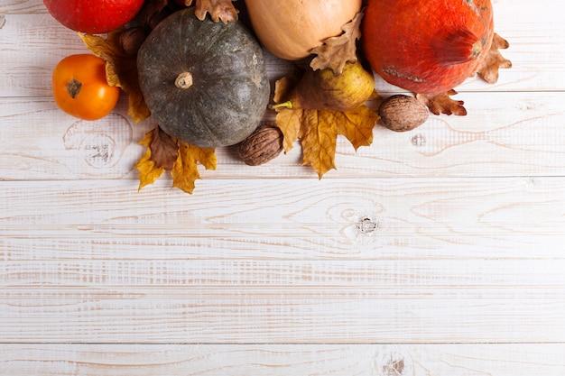 Verschillende groenten, pompoenen, appels, peren, noten, tomaten en droge bladeren op een witte houten achtergrond. herfststemming, copyspace. oogst.