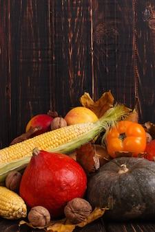 Verschillende groenten, pompoenen, appels, peren, noten, tomaten, maïs, droge gele bladeren op houten achtergrond. herfststemming, copyspace. oogst.
