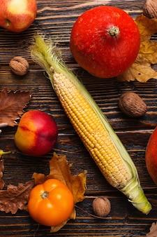 Verschillende groenten, pompoenen, appels, peren, noten, tomaten, maïs, droge gele bladeren op houten achtergrond. herfststemming, platliggend. oogst.