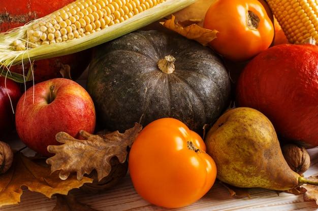 Verschillende groentenpompoenen, appels, peren, noten, maïs, tomaten, droge gele bladeren op witte houten achtergrond. herfstoogst, copyspace.