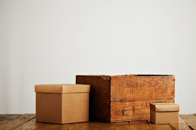 Verschillende grootte lege beige golfkartonnen dozen met deksels naast een vintage wijnkrat op wit wordt geïsoleerd