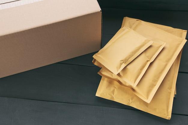 Verschillende grootte van papieren enveloppen en kartonnen doos op houten tafel