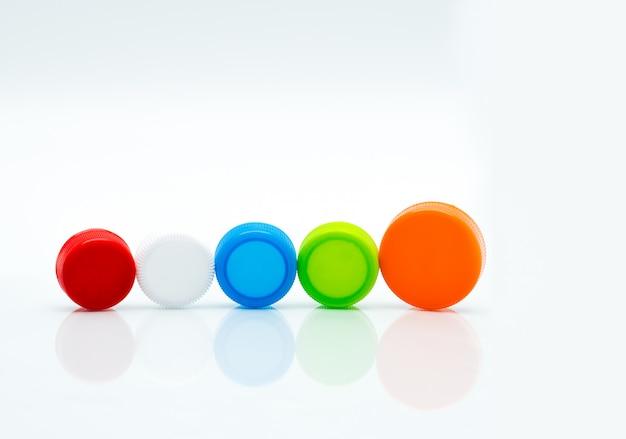 Verschillende grootte van witte, groene, rode, blauwe en oranje kleur ronde plastic schroefdoppen in een lijn