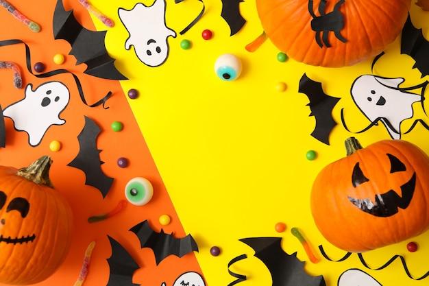 Verschillende halloween-accessoires en pompoenen op tweekleurige achtergrond