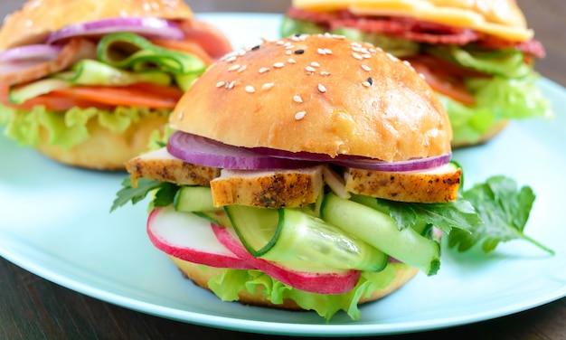 Verschillende hamburgers op het bord. zelfgemaakt broodje met ham of vlees of salami, groenten, kruiden. broodjes voor de lunch.