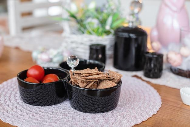 Verschillende hapjes in de borden staan op de bruine tafel in de keuken