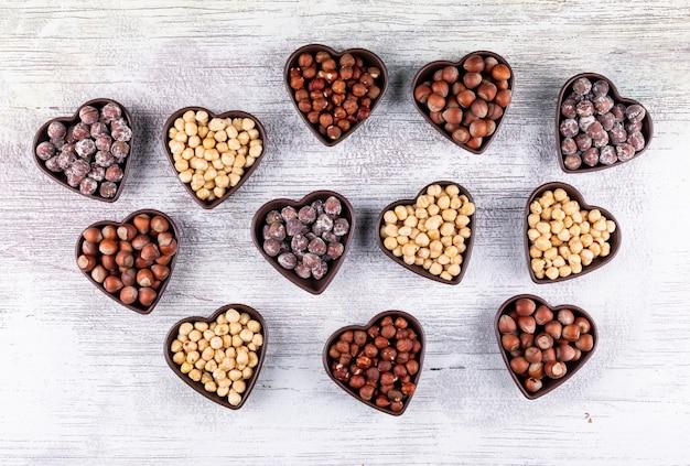 Verschillende hazelnoten in een hartvormige kommen bovenaanzicht op een witte houten tafel