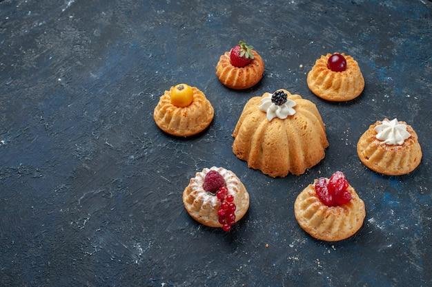 Verschillende heerlijke taarten met room en bessen op donkere vloer bessen fruit bakken cake koekje zoet