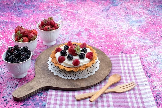 Verschillende heerlijke taarten met room en verse bessen op lichtpaars
