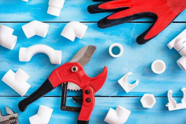 Verschillende hoeken, adapters en koppelingen samen met handschoenen en een pijpsnijder voor kunststof buizen.