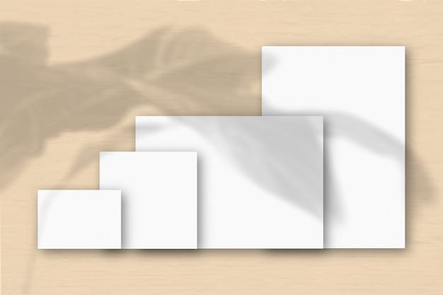 Verschillende horizontale en verticale vellen wit gestructureerd papier tegen een gele muurachtergrond. mockup met een overlay van plantschaduwen. natuurlijk licht werpt schaduwen van een tropische plant