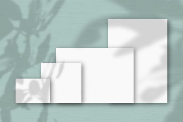 Verschillende horizontale en verticale vellen wit gestructureerd papier tegen een grijze muurachtergrond. mockup met een overlay van plantschaduwen. natuurlijk licht werpt schaduwen van de boom van geluk.