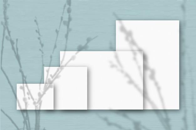 Verschillende horizontale en verticale vellen wit gestructureerd papier tegen een grijze muurachtergrond. mockup met een overlay van plantschaduwen. natuurlijk licht werpt schaduwen van wilgentakken.