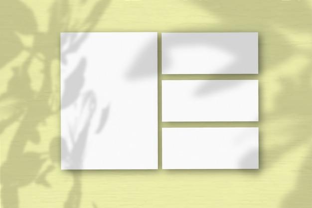 Verschillende horizontale en verticale vellen wit getextureerd papier op de achtergrond van een gele muur. natuurlijk licht werpt schaduwen van de boom van geluk. plat lag, bovenaanzicht. horizontale oriëntatie