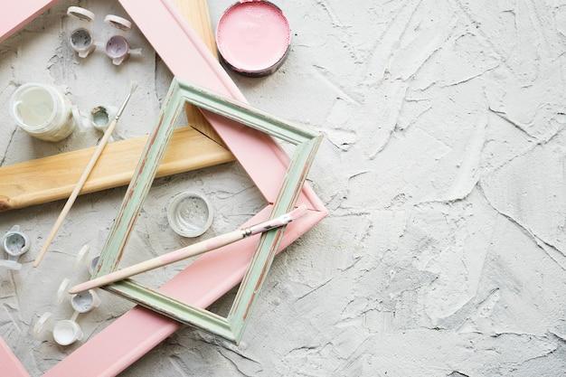 Verschillende houten frames, penselen en verfblikken op grijze grijze achtergrond met kopie ruimte. atelier van de kunstenaar.