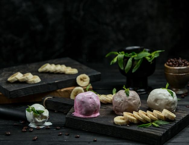 Verschillende ijsballen met plakjes banaan