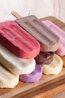 Verschillende ijslollys worden op de achtergrond van de houten plank geplaatst. verscheidenheid aan smaken en kleuren.
