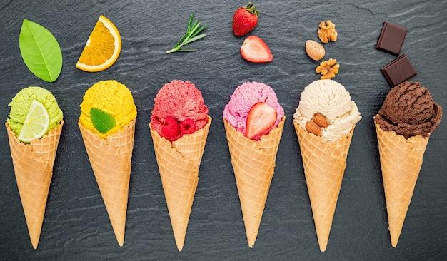 Verschillende ijssmaak in kegels bosbes, limoen, pistache, amandel, sinaasappel, chocolade, vanille en koffie opgezet op donkere stenen achtergrond. zomer en zoet menuconcept.