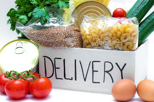 Verschillende ingeblikt voedsel, pasta en granen in een kartonnen doos. voedsel donaties of voedselbezorging concept. op wit wordt geïsoleerd. levering aan huis met coronovirus.