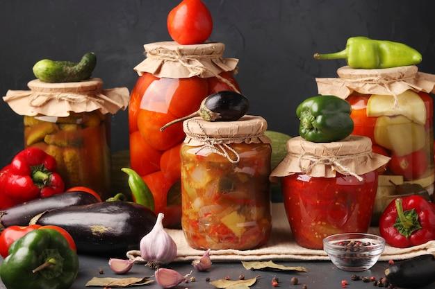 Verschillende ingemaakte groenten in glazen potten voor langdurige opslag: salade met aubergine, paprika in tomatensaus, komkommers, tomaten en gemengde groenten tegen een donkere ondergrond, horizontaal formaat