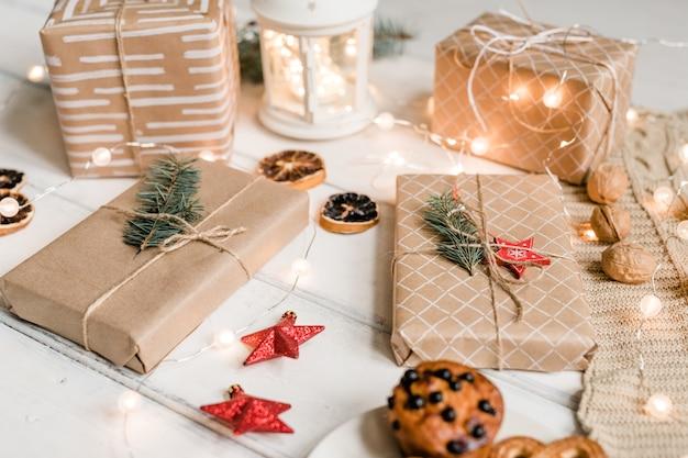 Verschillende ingepakte geschenken onder decoratieve rode sterren, walnoten, sprankelende slingers, schijfjes citroen en koekjes op witte tafel