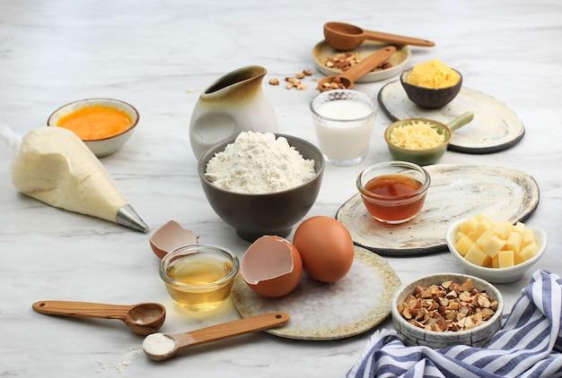 Verschillende ingrediënten voor het bakken van voorbereiding op marmeren tafel. meel, ei, room, honing en gehakte amandel klaar om bakmixbeslag te maken