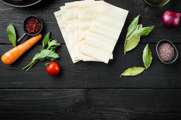 Verschillende ingrediënten voor lasagne-set, op zwarte houten tafelachtergrond, bovenaanzicht, plat gelegd, met kopieerruimte voor tekst