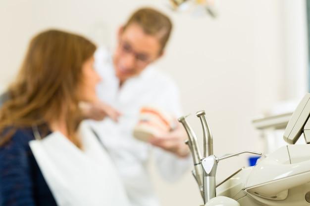 Verschillende instrumenten van een tandarts die wacht op de operatie, in de tandarts geeft een vrouwelijke patiënt een behandeling