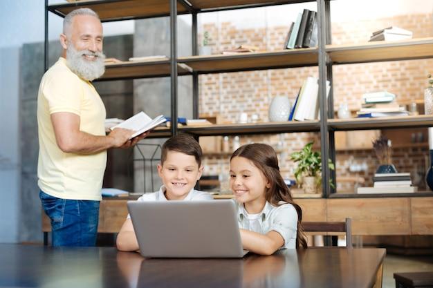 Verschillende interesses. schattige pre-tiener broer en zus zitten aan tafel en kijken naar een video terwijl hun grootvader een boek leest