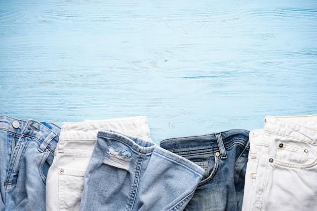 Verschillende jeans broek op een blauwe houten tafel, bovenaanzicht. ruimte voor tekst.