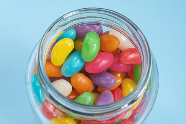 Verschillende jelly beans op de blauwe achtergrond in de glazen pot