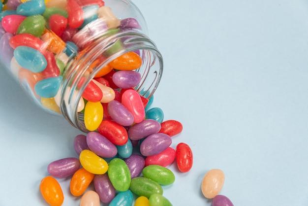 Verschillende jelly beans op het blauwe oppervlak in de glazen pot
