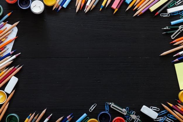 Verschillende kantoorbenodigdheden op donkere tafel, creatieve educatieve achtergrond voor website met kleurpotloden, verven op zwart houten bureau, terug naar schoolconcept, 1 september, bovenaanzicht, kopie ruimte