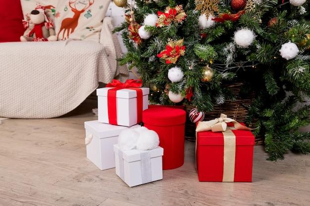 Verschillende kerstcadeautjes met handgemaakte decoratie. verpakt in rode papieren huidige dozen onder kerstboom.
