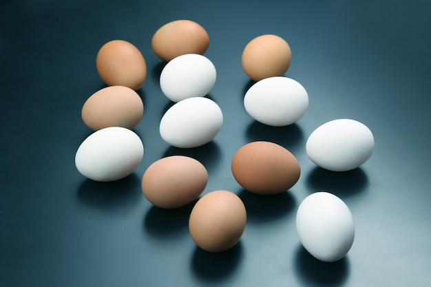 Verschillende kippeneieren liggen op donker