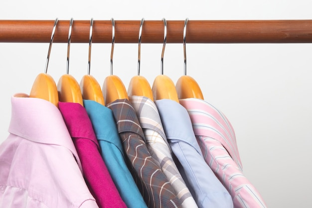 Verschillende klassieke damesoverhemden voor op kantoor hangen aan een hanger om kleding in op te bergen