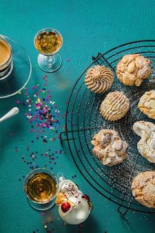 Verschillende klassieke italiaanse zelfgemaakte amandelkoekjes met espresso koffie en glazen zoete drank op tafel, kerst decor