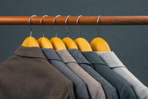 Verschillende klassieke kantoorjassen voor dames hangen aan een hanger om kleding in op te bergen. de stijlkeuze van modieuze kleding