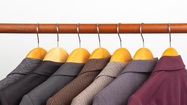 Verschillende klassieke kantoorjassen voor dames hangen aan een hanger om kleding in op te bergen