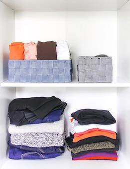 Verschillende kleding in huisgarderobe met aantekeningen op papier. kleine ruimte organisatie. verticale opslag.