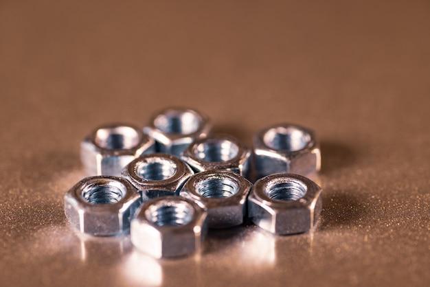 Verschillende kleine glanzende moeren op metalen oppervlak van een niet-geïdentificeerde fabrieksuitrusting. het concept van geavanceerde apparatuur en moderne technologie.