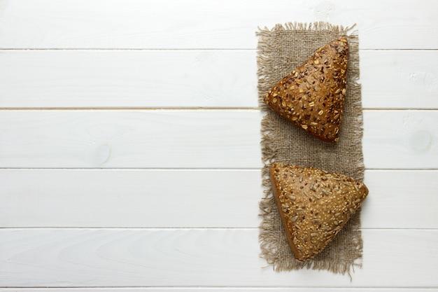 Verschillende kleine meergranen driehoekig brood bestrooid met hele zonnebloempitten, vlas en sesamzaadjes op een zak