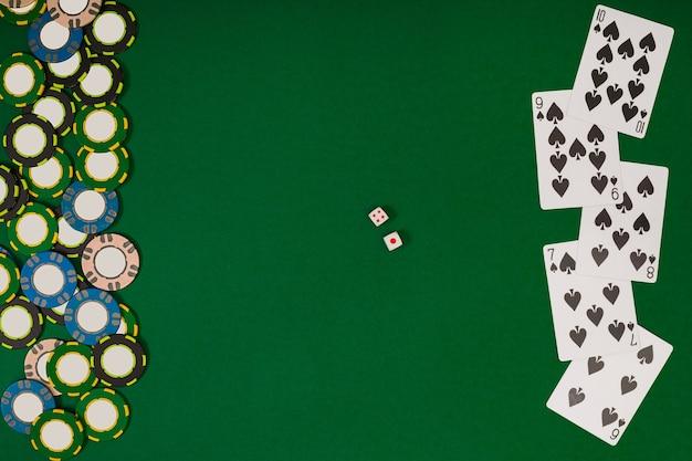 Verschillende kleur chips voor gokken en speelkaarten op groene achtergrond. bovenaanzicht. stilleven. ruimte kopiëren