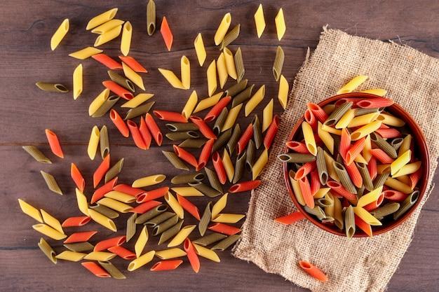 Verschillende kleuren pasta in plaat bovenaanzicht op rouwgewaad op houten oppervlak