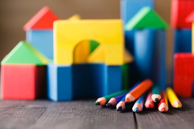 Verschillende kleurenpotloden op lijst met bouwstenen