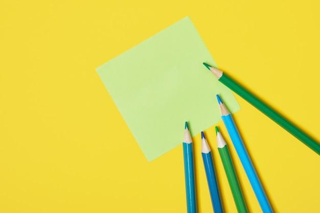 Verschillende kleurpotloden en plaknotities op gele achtergrond kopie ruimte bovenaanzicht