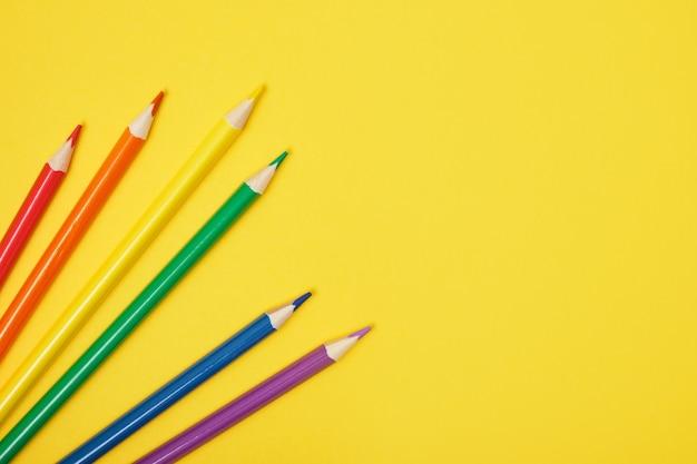 Verschillende kleurpotloden op een gele achtergrond kopie ruimte bovenaanzicht