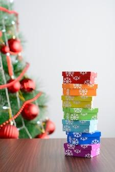 Verschillende kleurrijke geschenkdozen op tafel bij dennenboom op bruine achtergrond.