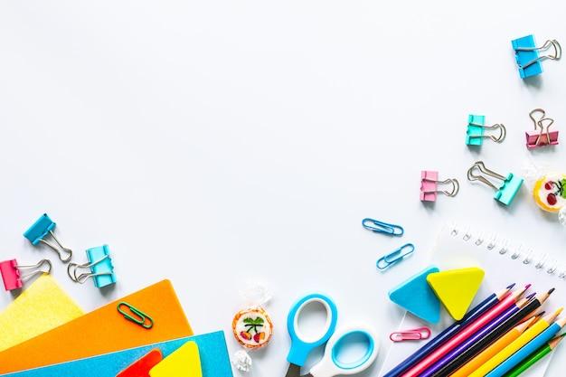 Verschillende kleurrijke kantoorbehoeften voor school op witte achtergrond met copyspace.