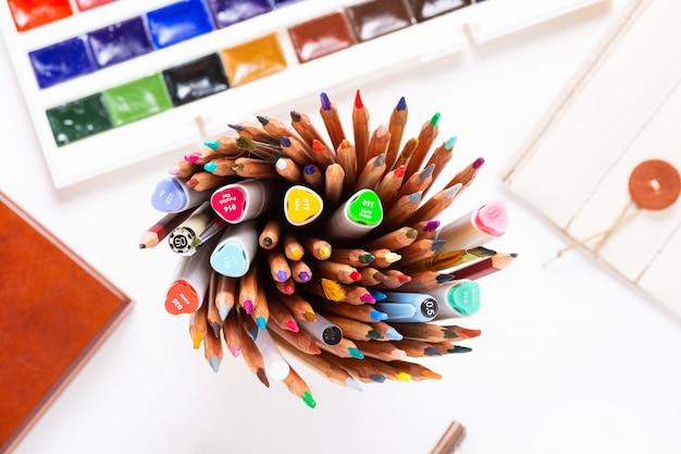 Verschillende kleurrijke markeringen en potloden met accessoires op witte office tafel
